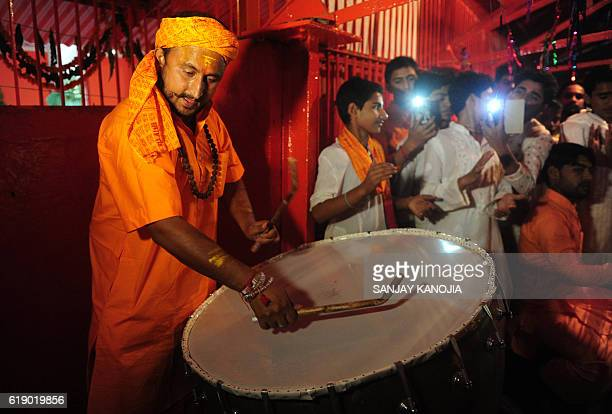 An Indian priest beats a drum during Arti at the Bade Hanuman Temple on the occasion of Hanuman Jayanti near Sangam in Allahabad on October 29 2016...