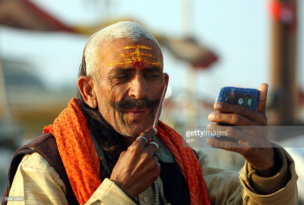 "An Indian priest combs his moustache on the bank of ""Sangam,"" the confluence of the three rivers Ganges, Yamuna and mythical Saraswati in Allahabad on December 21, 2012. The Kumbh Mela, which is scheduled to take place in the northern Indian city in January and February 2013, is the world's largest gathering of people for a religious purpose and millions of people gather for this auspicious occasion. AFP PHOTO/ Sanjay KANOJIA"