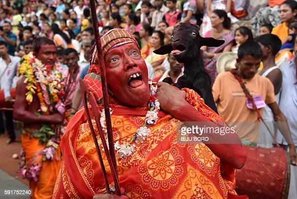 An Indian priest dances as he carries a sacrificial goat during the Deodhani Festival at the Kamakhya Temple in Guwahati the capital city of the...