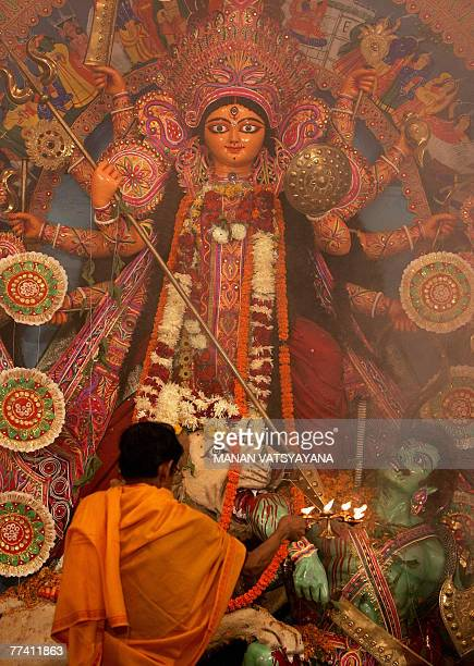 An Indian priest offers prayers to the idol of Hindu goddess Durga during the Durga Puja festival in New Delhi 19 October 2007 Goddess Durga who...