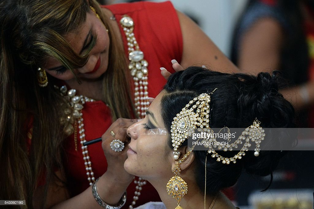 An Indian professional make-up artist participates in a bridal make-up competition at the 7th International Beauty and Spa Expo in New Delhi on June 28, 2016. The expo is billed as India's largest beauty products trade show. / AFP / PRAKASH