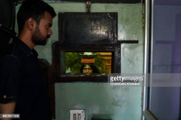 An Indian projectionist looks on inside the projection room of a local movie theatre in Kekri some 78 kms south of Ajmer on May 14 in the northern...
