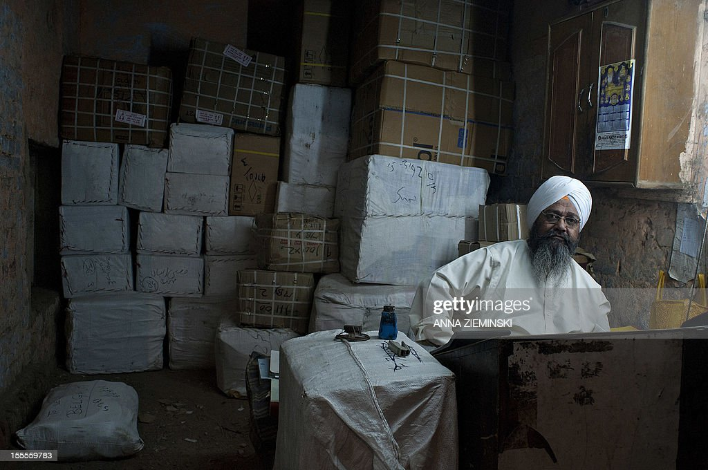 An Indian proprietor of a parcel service sits in his shop in New Delhi on November 5, 2012. The ruling Congress party has rolled out its big guns to defend the move to let the likes of Walmart set up shop in India, but they are confronting an alliance stretching across the political spectrum. Prime Minister Manmohan Singh's left-leaning government announced in September that it was lowering the bar for foreign firms to operate in sectors ranging from retail to insurance, in a bid to revive its fortunes before elections in 2014 but elsewhere in the country, a broad array of Congress opponents are vowing to scupper the changes. AFP PHOTO/Anna ZIEMINSKI