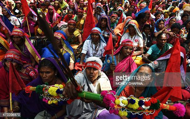An Indian protester holds a bow and arrow as she sits with others during a rally in New Delhi on May 5 against the ruling governments proposed land...