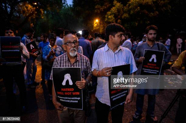 An Indian protester holds a placard during a 'Not In My Name' silent protest over an attack on pilgrims taking part in the Amarnath Yatra in New...