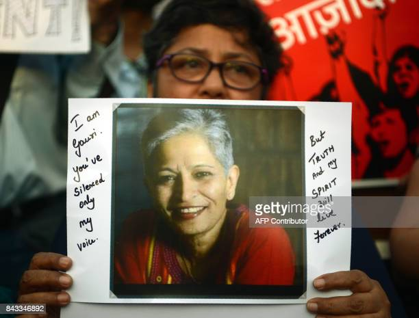 An Indian protester holds a placard in a rally condemning the killing of journalist Gauri Lankesh in Mumbai on September 6 2017 Indian activists...