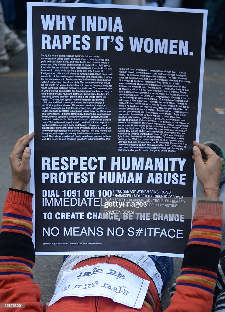 An Indian protestor holds a placard as he lies on a road during a protest demanding better security for women in New Delhi on December 29, 2012, after the death of a gangrape victim from the Indian capital New Delhi. Indian leaders appealed for calm and security forces headed off fresh unrest by turning New Delhi into a fortress after a student who was savagely gang-raped died in a Singapore hospital. Police threw a ring of steel around the centre of the Indian capital after news of the 23-year-old medical student's death was broken in the early hours by the Singapore hospital that had been treating her for the last two days.