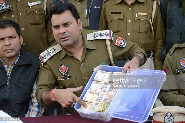 An Indian Punjab Police officer display 500 and 1000 rupee notes recovered from Faizabad resident Rajiv Kumar during a press conference in Amritsar...
