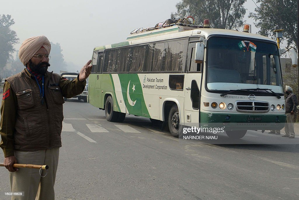 An Indian Punjab state policeman stands guard as a bus from Pakistani passes on the outskirts of Amritsar on January 29, 2013. Indian Punjab police arrested 30 members of Shiv Sena as they tried to stop buses from Pakistan during a protest against the killing of two Indian soldiers in the disputed Kashmir region.