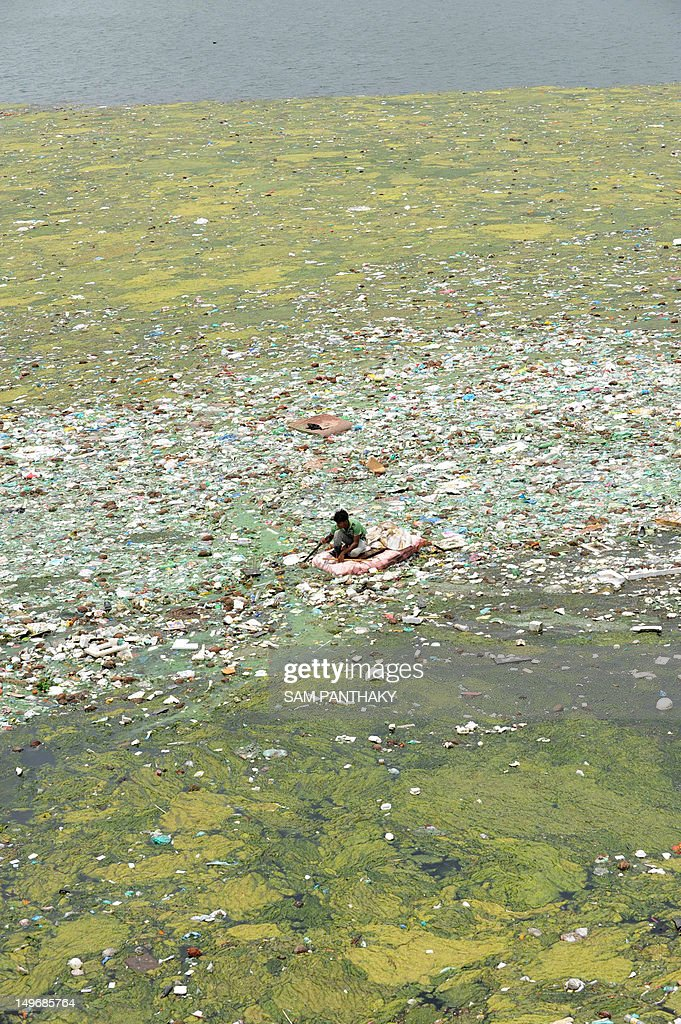 An Indian rag picker searches for reusable items by floating on a makeshift raft in the polluted Sabarmati river in Ahmedabad on August 2, 2012. Terming water pollution as a 'national crisis', a Parliamentary committee has decided to summon officials of at least six central ministries to seek their views to find ways to check the problem according to PTI. AFP PHOTO / Sam PANTHAKY