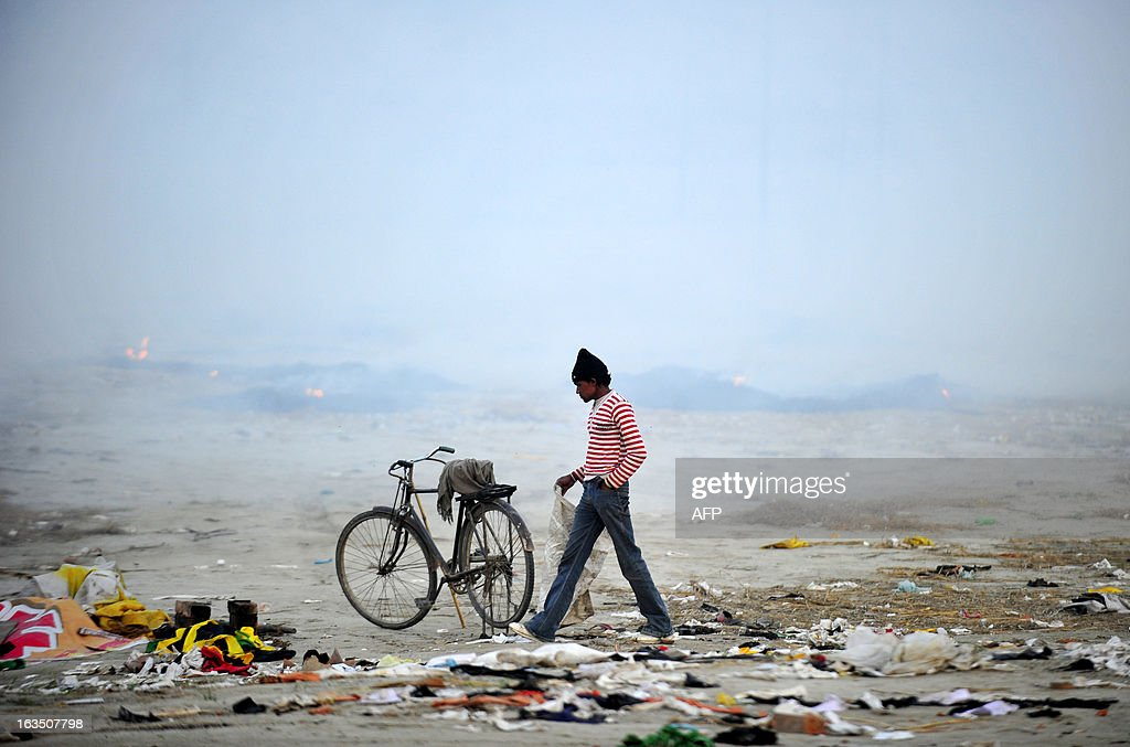 An Indian ragpicker collects recycleable material from camping grounds near the Sangam following the conclusion of the Kumbh Mela in Allahabad on March 11, 2013. The Sangam is a holy bathing site during The Kumbh Mela, which runs from January till March, and takes place every 12 years in Allahabad while smaller events are held every three years in other locations around India. AFP PHOTO/Sanjay KANOJIA