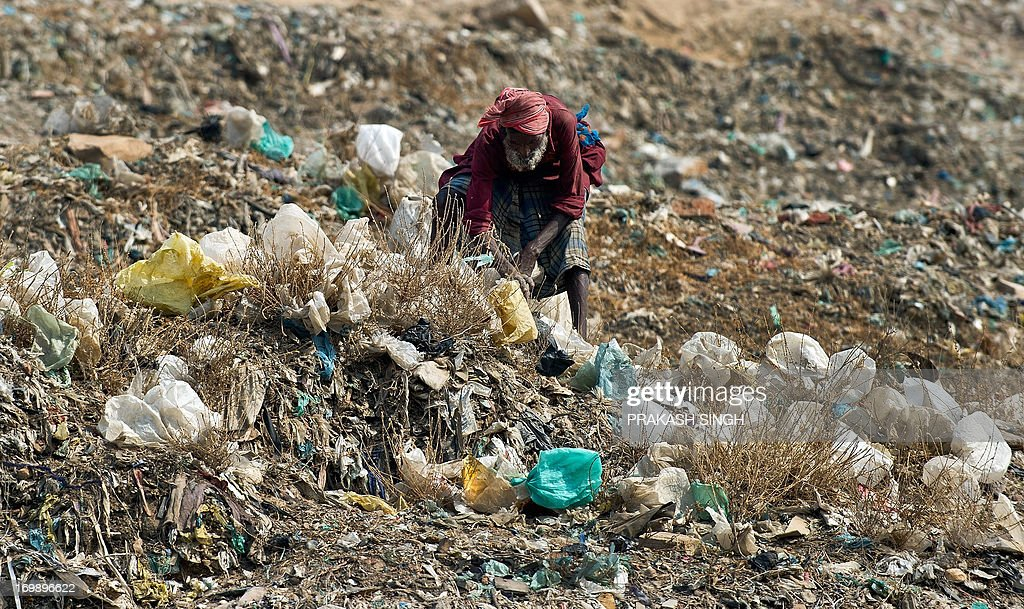 An Indian ragpicker looks for recyclable materials on the ridge of one of the capital's garbage landfills at Gazipur in New Delhi on June 4, 2013, on the eve of World Environment Day. As per newspaper reports, the Indian capital produces 9,000 tons of garbage daily. India's cities are becoming more polluted and unhealthy, according to a new survey published Monday showing growing concern about the impact of high economic growth on the environment. AFP PHOTO/ Prakash SINGH