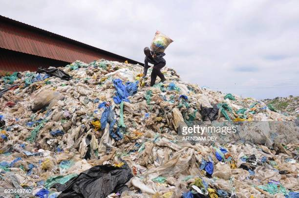 An Indian ragpicker searches for recyclable items at a plastic recycling station in Agartala the capital of the northeastern state of Tripura on June...