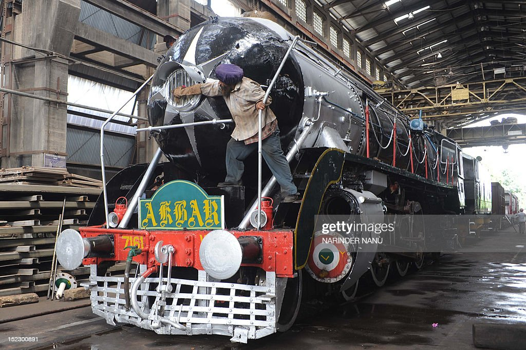 An Indian railway worker Sukhdev Singh cleans dust from the one of the most popular heritage steam rail engines called 'Akbar' after the great Mughal emperor, currently under repair at the Railway Workshop in Amritsar on September 18, 2012. 'Akbar', made by a Canadian Locomotive Company nearly 80 years ago, will soon start delighting tourists with joy rides between Delhi Cantt and Alwar from November 2012 till April 2013 senior railways officials said.