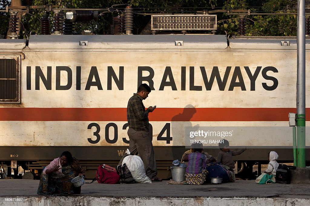 An Indian Railways train engine moves past waiting travellers on a platform at the Hazrat Nizamuddin railway station in New Delhi on February 26, 2013, when the railway budget is due to be tabled in Parliament. The railway, the country's largest employer with some 1.4 million people on its payroll, runs 11,000 passenger and freight trains and carries 19 million people daily. AFP PHOTO / TENGKU BAHAR