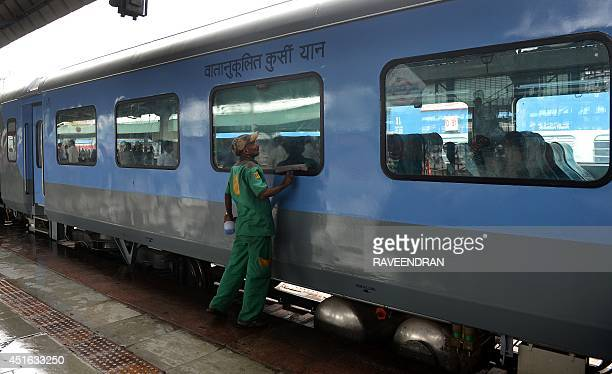 An Indian railways worker cleans a coach prior to the trial run of a highspeed train between New Delhi and Agra is flagged off at New Delhi railway...