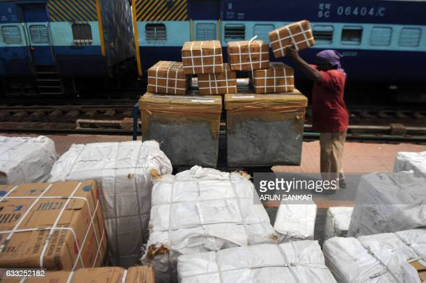 An Indian railways worker lifts parcels onto a cart before loading them onto a train at a station in Chennai on Febuary 1 2017 India is to halve the...