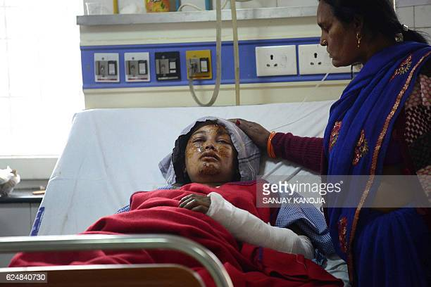 TOPSHOT An Indian relative assists an injured train passenger at a hospital in Kanpur on November 21 2016 Rescuers on November 21 ended their search...