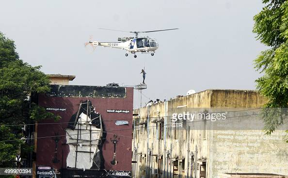An Indian rescue helicopter lifts a man off a roof of apartment buildings surrounded by floodwaters in Chennai on December 4 2015 Thousands of...
