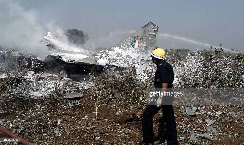 An Indian rescue worker walks in front of a burning Indian Air Force (IAF) MiG 29 aircraft, which crashed near Jamnagar airbase, some 350 kms from Ahmedabad on November 8, 2013. The pilot, who was airborne on a routine flying training sortie, ejected safely. There is no reported damage on the ground to any civil life or property and a Court of Inquiry has been ordered to investigate the cause of the accident.