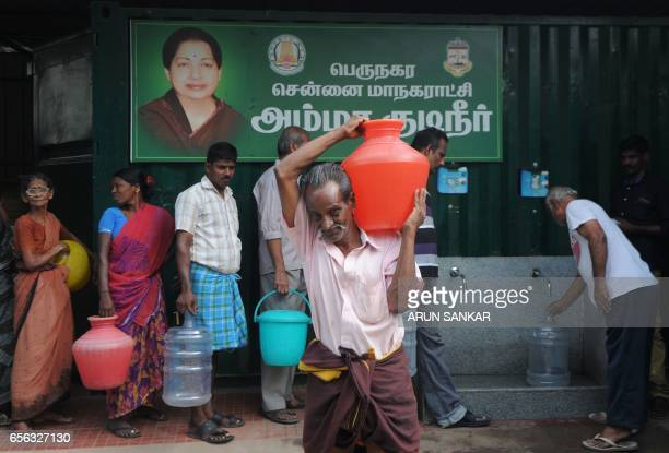 An Indian resident carries a plastic container full of purified drinking water after collection from a government distribution centre in Chennai on...