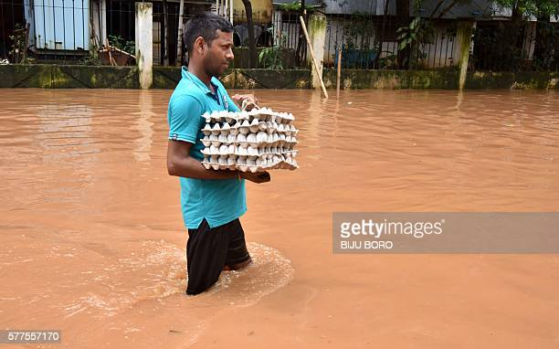 TOPSHOT An Indian resident carries a tray of eggs as he wades through floodwaters in the Anilnagar area of Guwahati on July 19 2016 Floods in the...