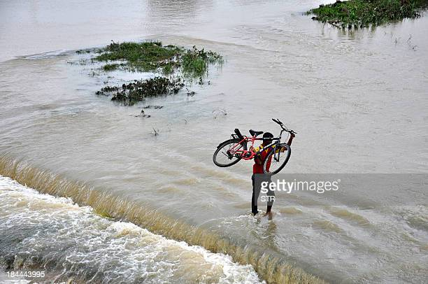 An Indian resident carries his bicycle through the waters of the overflowing Swarnrekha river following heavy rains due to Cyclone Phailin at Gaghra...