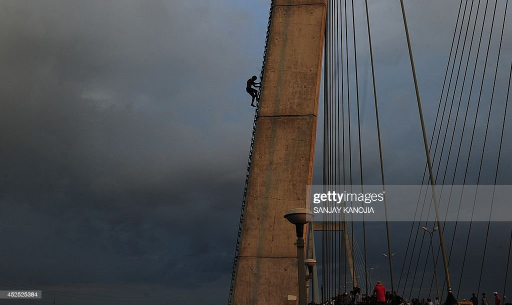 An Indian resident climbs down from a bridge accross the Yamuna near Sangam in Allahabad on July 22 2014 Police detained the man after a threehour...