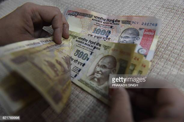 An Indian resident counts 500 and 1000 INR notes at her home in New Delhi on November 8 2016 Indian Prime Minister Narendra Modi announced late...