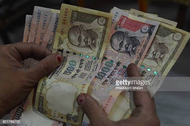 An Indian resident holds 500 and 1000 INR notes in New Delhi on November 8 2016 Indian Prime Minister Narendra Modi announced late November 8 that...