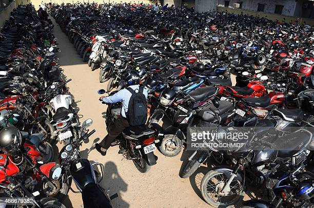 An Indian resident looks for a spot to park his motorbike in a crowded parking lot at a metro station in New Delhi on March 18 2015 AFP PHOTO /...