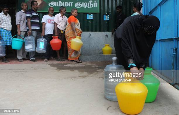 An Indian resident prepares to carry plastic containers full of purified drinking water after collection from a government distribution centre in...