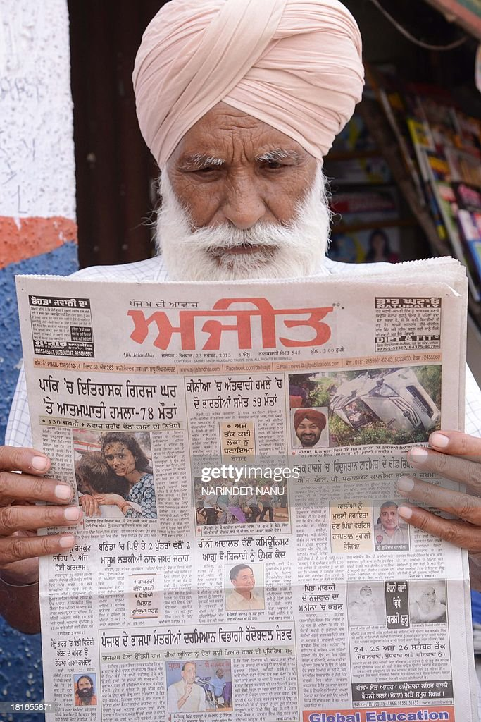 An Indian resident reads a newspaper, displaying front page headlines of attacks on Christians in Pakistan, at a roadside stall in Amritsar on September 23, 2013. The death toll from a double suicide bombing on a church in Pakistan rose to 81, as Christians protested across the country to demand better protection for their community. The attack on All Saints church in the northwestern city of Peshawar after a service on September 22, which has been claimed by the Pakistani Taliban, is believed to be the deadliest ever to target Pakistan's small Christian minority. AFP PHOTO/NARINDER NANU