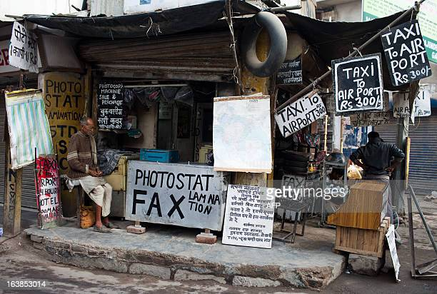 An Indian resident sits at a travel and documents stand in New Delhi on March 17 2013 Indian business leaders and the government have for months been...