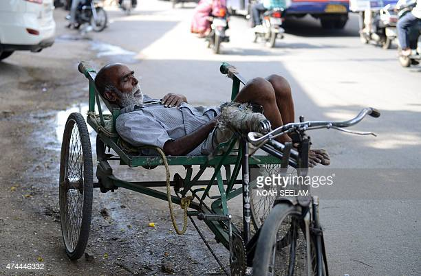 An Indian resident sleeps in the shade on a tricyle at the roadside in Hyderabad on May 22 2015 High temperatures in the southern state of Telangana...
