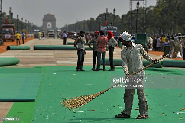 An Indian resident sweeps a carpet the start of the Clean India Campaign launched by Prime Minister Narendra Modi in New Delhi on October 2 2014...