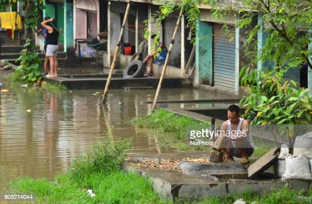 An Indian resident works in front of his submerge house after a heavy rainfall in Dimapur India north eastern state of Nagaland on Saturday 01 July...