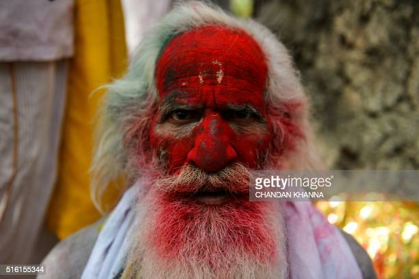 TOPSHOT An Indian reveler covered in coloured powder poses during the Lathmar Holi celebrations in the village of Barsana on March 17 2016 holi also...