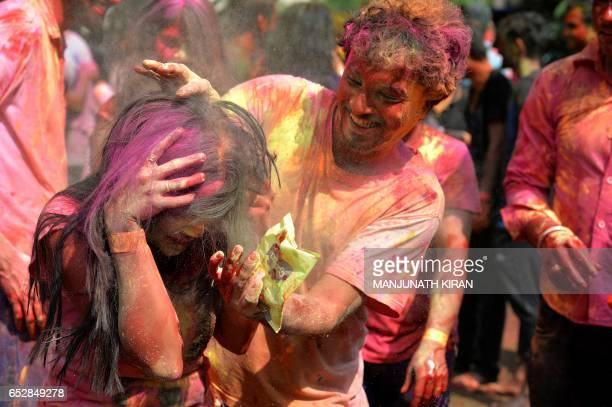 An Indian reveller reacts as a friend splashes coloured powder on her during Holi celebrations in Bangalore on March 13 2017 Holi the festival of...
