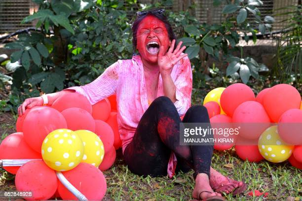 An Indian reveller reacts as a friend splashes coloured water on her during Holi celebrations in Bangalore on March 13 2017 Holi the festival of...