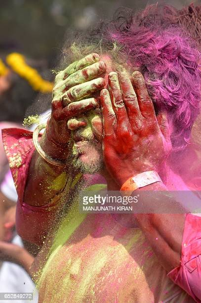 An Indian reveller reacts as he is smeared with coloured powder by a friend during Holi celebrations in Bangalore on March 13 2017 Holi the festival...
