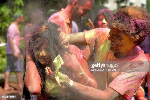 An Indian reveller reacts as she is smeared with coloured powder by a friend during Holi celebrations in Bangalore on March 13 2017 Holi the festival...
