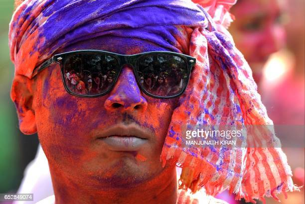 An Indian reveller smeared with coloured powder looks on during Holi celebrations in Bangalore on March 13 2017 Holi the festival of colours is a...