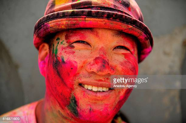 An Indian reveller smeared with coloured powder takes part in the Holi Festival celebrations in Mathura India on March 18 2016 Holi the festival of...
