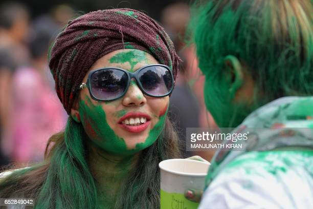 An Indian reveller with her face smeared with coloured powder chats with a friend during Holi celebrations in Bangalore on March 13 2017 Holi the...
