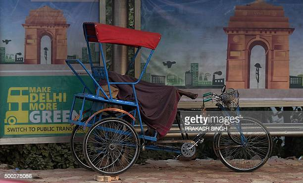 An Indian rickshaw cyclist sleeps next to an advertisement for a more environmentally friendly city urging residents to switch to public transport on...