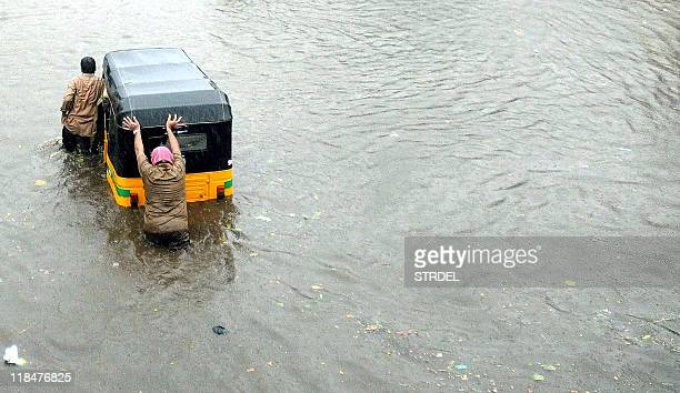 An Indian rickshaw driver pushes his vehicle through floodwaters in Chennai on May 19 during heavy rain ahead of the arrival of Cyclone Laila A...
