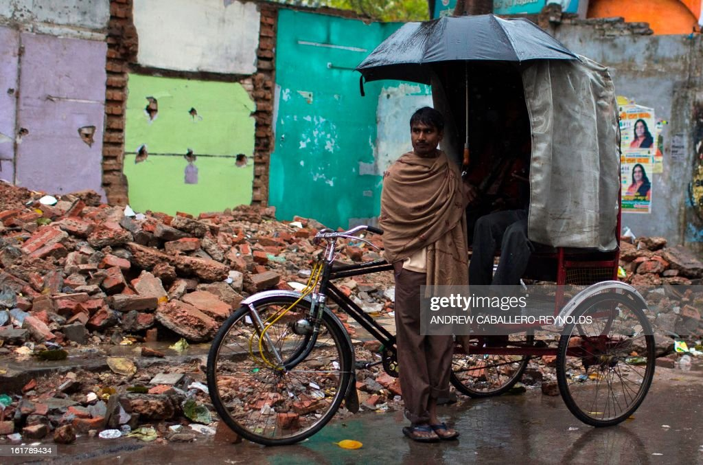 An Indian rickshaw driver takes shelter from the rain near the Sangam during a rain shower in Allahabad on February 16, 2013. The Kumbh Mela in the town of Allahabad will see up to 100 million worshippers gather over 55 days to take a ritual bath in the holy waters, believed to cleanse sins and bestow blessings. AFP PHOTO/ Andrew Caballero-Reynolds