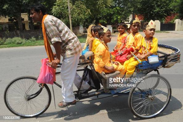 An Indian rickshaw driver transports children dressed as Hindu God Lord Krishna from school in Amritsar on August 9 2012 on the eve of the...