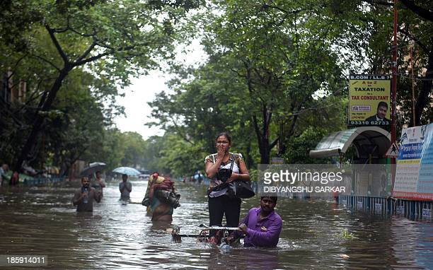 An Indian rickshaw puller carries a student through waterlogged streets in Kolkata on October 26 2013 Persistent rain for the last 24 hours has...
